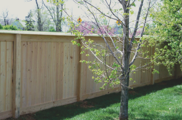 wooden-fence-with-natural-wood-stain-on-green-grass-with-nice-landscaping