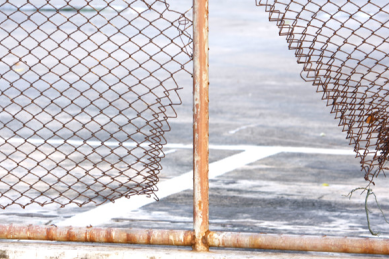 rusty-metal-chain-link-fence-that-needs-fixed-and-repaired